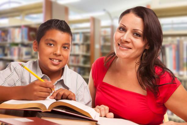 Hispanische junge und weibliche Erwachsene Studium an der Bibliothek – Foto
