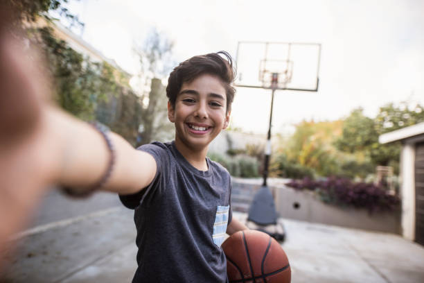 hispanic young boy taking a selfie and holding a basketball in his hands - self portrait photography stock pictures, royalty-free photos & images