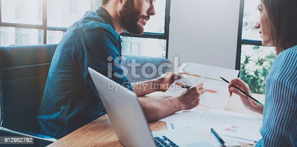 istock Hispanic young businessman working with business partner at sunny office.Blurred background. Horizontal.Cropped. 912952782