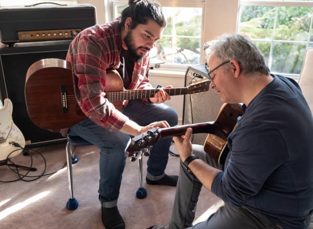 Hispanic Young Man Teaching Mature Caucasian Man to Play Guitar stock photo