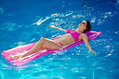 A Hispanic young woman vacationing in Cancun Mexico, Relaxing in swimming pool.