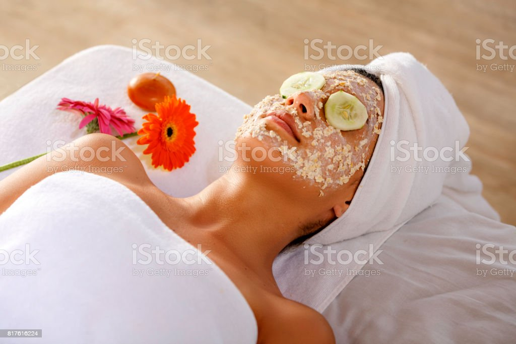 Hispanic young woman laying on bed and getting oatmeal face scrub and resting with cucumber slices on eyes. stock photo