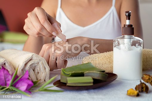 Hispanic young woman moisturizing hands with aloe vera natural gel