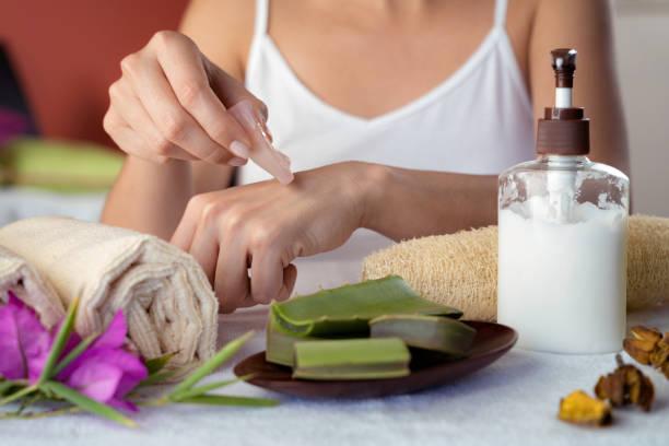 Jeune femme hispanique hydratant des mains avec le gel normal d'aloe vera - Photo