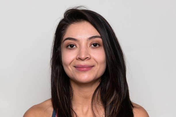Hispanic young woman posing on gray background stock photo