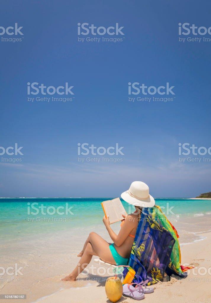 Mulher jovem hispânica, lendo um livro sobre uma praia tropical ilha de areia branca, no mar do Caribe - foto de acervo