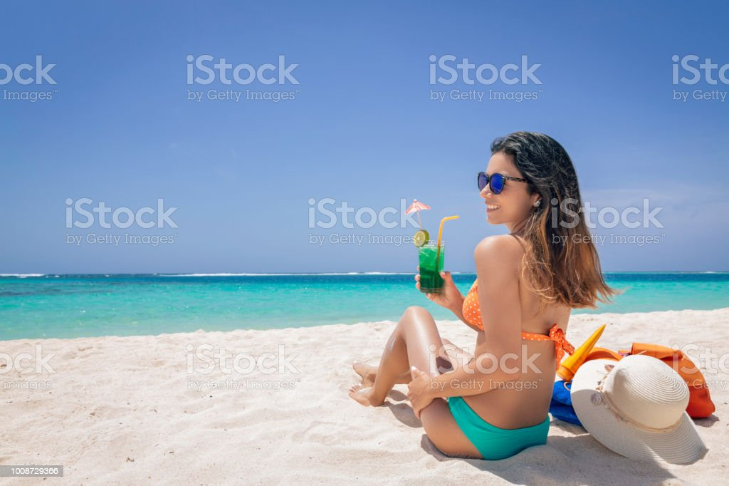 Hispanic Young woman refreshing with a alcohol drink in a tropical white sand island beach in the Caribbean sea stock photo