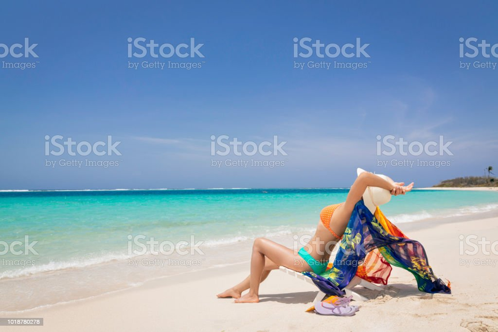 Hispanic Young woman relaxing and resting on a tropical white sand island beach in the Caribbean sea stock photo