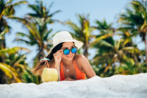 Hispanic young woman sunbathing and applying sunscreen on a tropical white sand island beach in the Caribbean sea stock photo