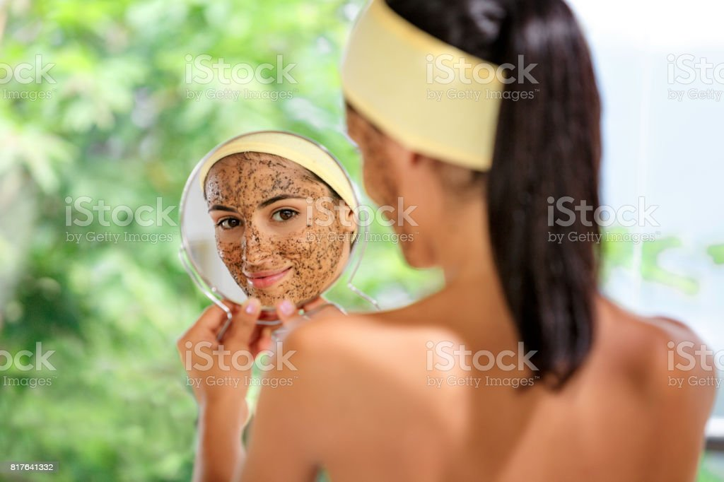 Hispanic young woman with coffe face scrub after bath looking at herself on hand mirror. Skin Exfoliation. stock photo