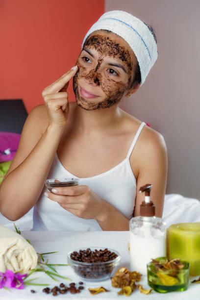 Jeune femme hispanique avec le gommage de visage de café après le bain regardant l'appareil-photo. Exfoliation de la peau. - Photo