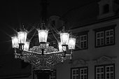 Detail of a historic and ornamental gas candelabrum in a street of Prague. Night image
