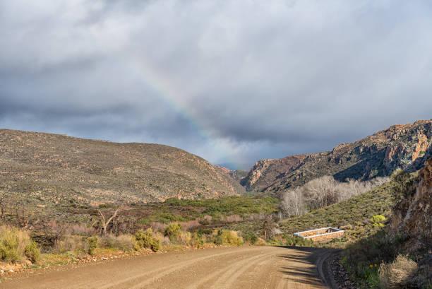 Cementerio histórico y un arco iris en la reserva natural de Matjiesrivier - foto de stock