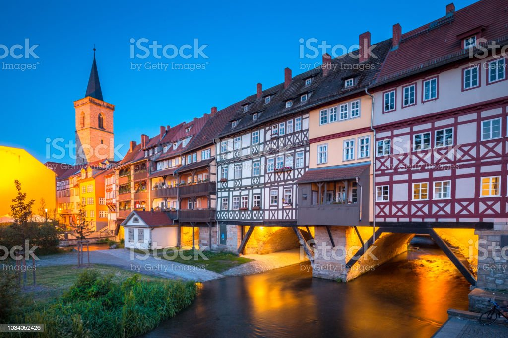 Historic city center of Erfurt with famous Kraemerbruecke bridge illuminated at twilight, Thueringen, Germany stock photo