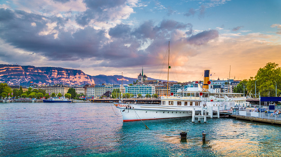 Historic city of Geneva with paddle steamer at sunset, Switzerland
