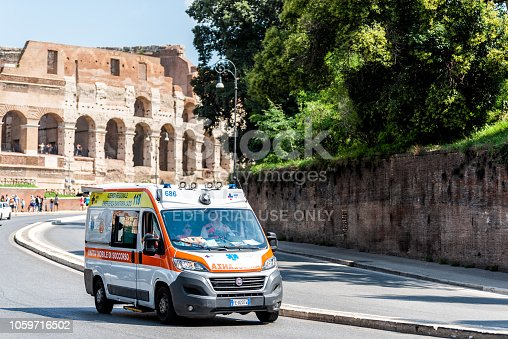 istock Historic city with ambulance emergency driving on road street by Colosseum, sunny summer day, people, stone walls of Amphitheatre architecture 1059716502