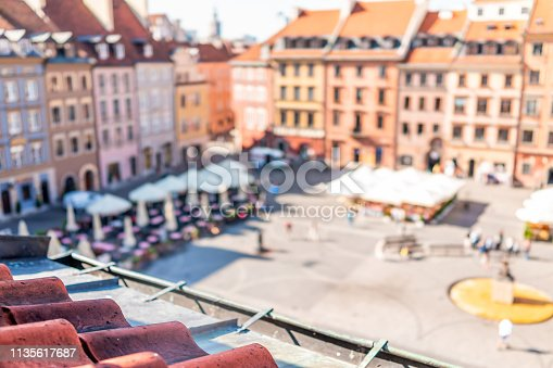 Historic cityscape skyline bokeh in Warsaw, Poland with roof tiles and high angle view of colorful architecture rooftop buildings in old town market square during sunrise