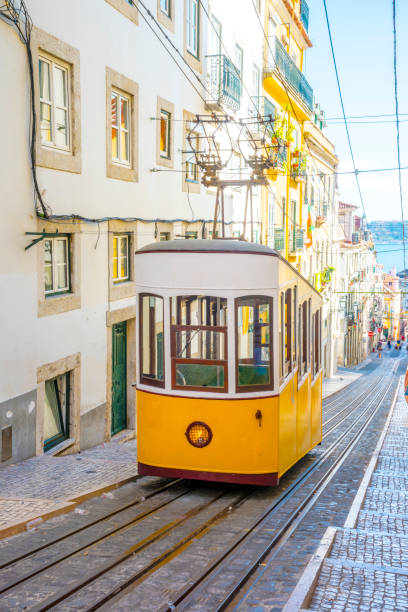 lisbon, portugal. a historic classic yellow tram of lisbon built partially of wood and being secured by cable while navigating through the steep and narrow streets of old lisbon - eletrico lisboa imagens e fotografias de stock