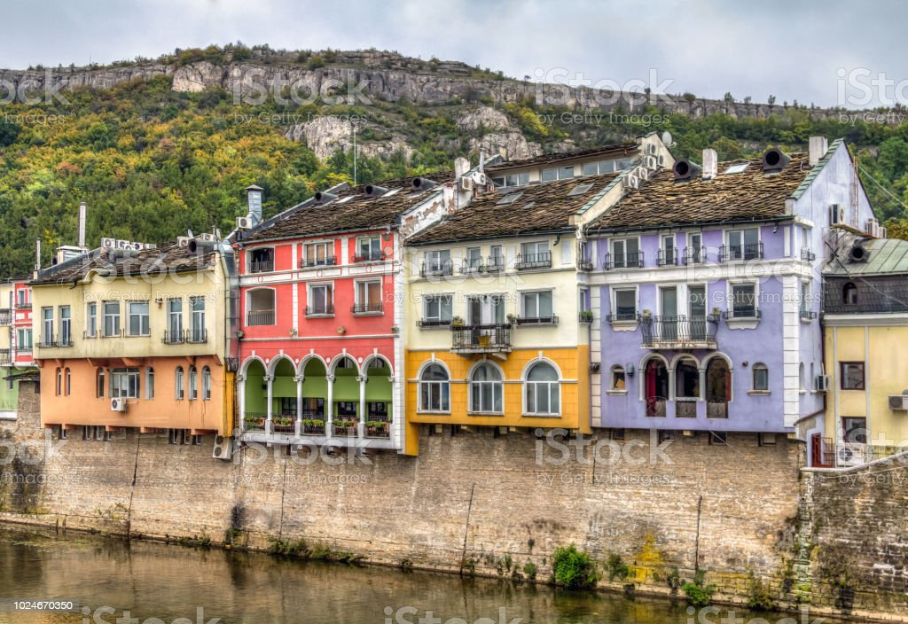 Historic colourful building facades in Lovech, Bulgaria. With Osam river in the front and mountain in background - Royalty-free Arcade Stock Photo