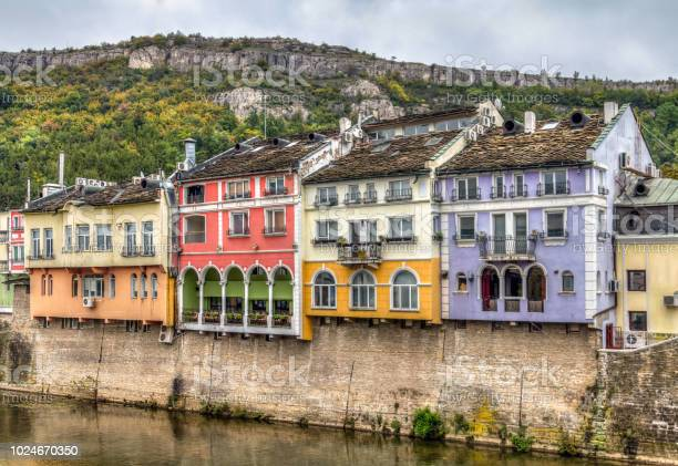 Historic Colourful Building Facades In Lovech Bulgaria With Osam River In The Front And Mountain In Background Stock Photo - Download Image Now