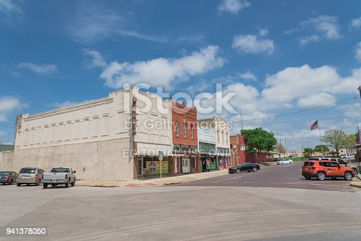 Ennis, Tx: Historic vintage building, street at downtown Ennis cloud blue sky. A city in eastern Ellis County, Texas 35 miles south Dallas. Best known for spring Bluebonnet festival