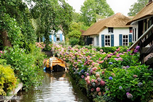 istock Historic Dutch houses with river, boat and many flowers 176083462