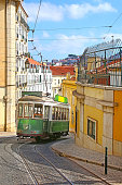 Historic green tram against old town streets, part of the tramway network since 1873, Lisbon, capital city of Portugal.