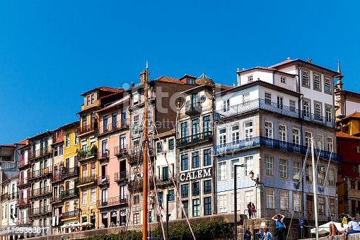 Porto, Portugal - September 27th, 2014: Historic house facades in the old city center on the banks of the Douro River with the building of the big Portwine Merchant Bodegas Calem amidst