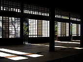 Historic home in Japan, the former mansion from an  influential shogun from a region near Tokyo, showing the intricate paper window panels set against incoming sunlight, causing a very delicate scene of light and shadow patterns on the wooden floor and against the paper windows and sliding doors.