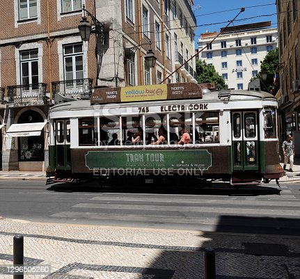 Lisbon, Lisbon, Portugal- June 2, 2019: Lisbon, Portugal historic streetcar filled with tourists moving in front of residential buildings.