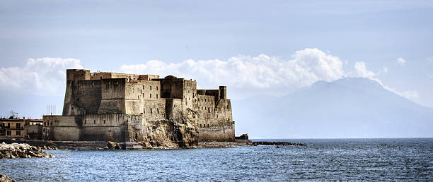Historic Naples Italy Panoramic photo of the Castel dell'Ovo in Naples, Italy with the famous Mount Vesuvius volcano in the background. Image composed of two separate photos stitched together. davelongmedia stock pictures, royalty-free photos & images