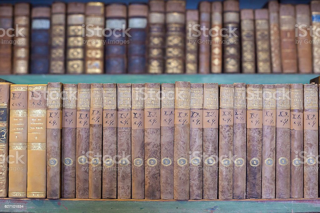 historic old books in library, wooden bookshelf stock photo