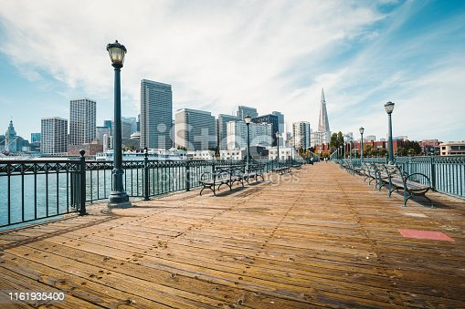 Classic view of historic Pier 7 with the modern financial district of San Francisco on a beautiful sunny day with blue sky and clouds in summer, California, USA