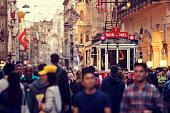 Tramway passing through large crowded Istiklal street in Taksim, Beyoglu, Istanbul, Turkey.