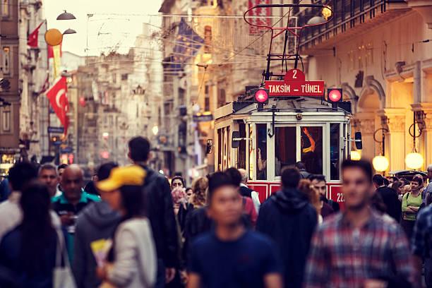 historic red tram on crowded istiklal avenue in taksim, istanbul - anadolu stok fotoğraflar ve resimler