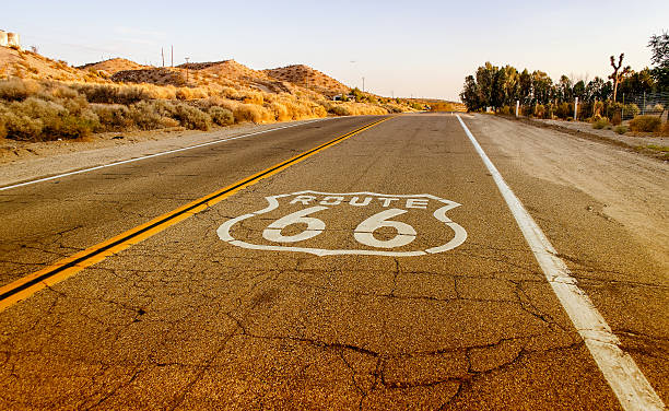 La storica Route 66 segno in California con pavimentazione - foto stock