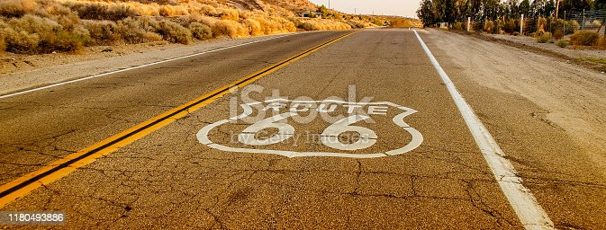 Historic Route 66, with pavement sign in California, USA. Route 66 is one of the most iconic roads in the world