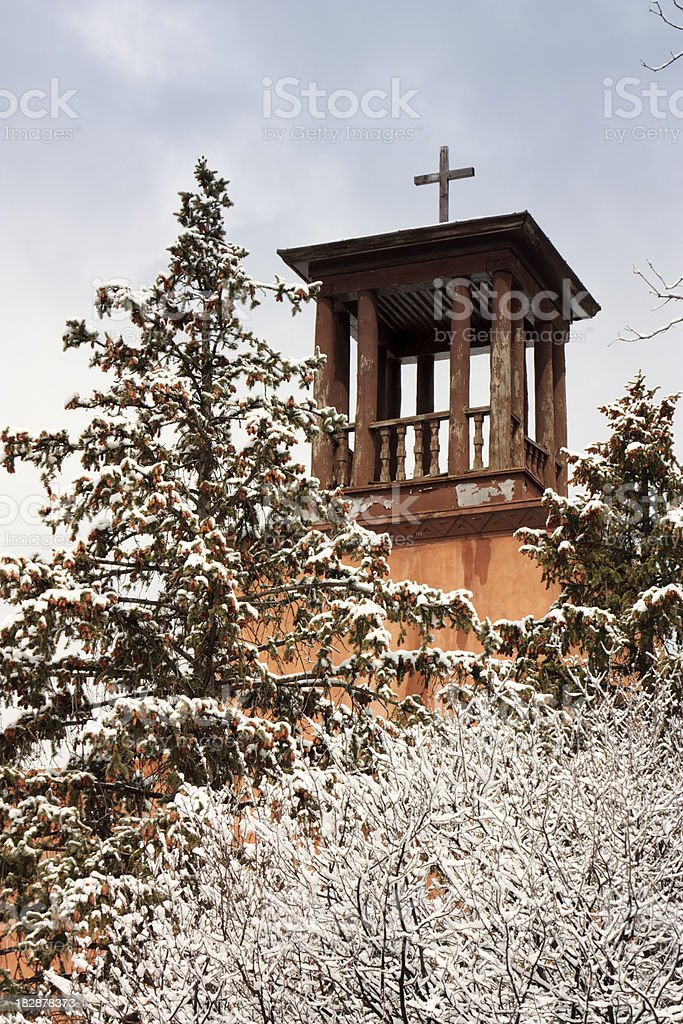 Historic Santa Fe Church Steeple Stands over snow covered trees royalty-free stock photo