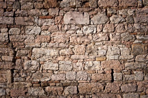 Wall of irregular stonea in historic italy.