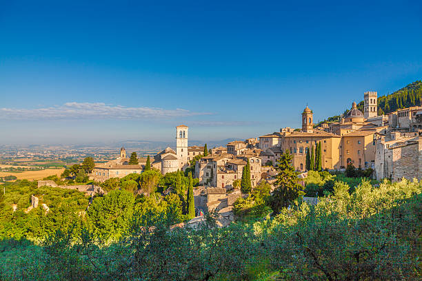 Historic town of Assisi at sunrise, Umbria, Italy Panoramic view of the historic town of Assisi in beautiful golden morning light at sunrise in summer, Umbria, Italy. umbria stock pictures, royalty-free photos & images