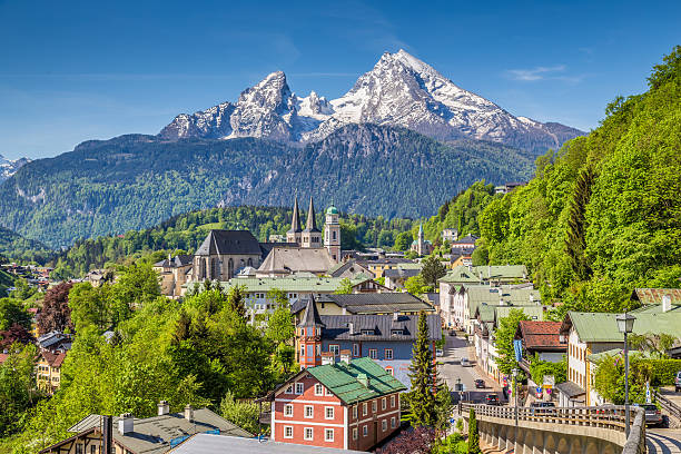 Historic town of Berchtesgaden with Watzmann mountain, Bavaria, Germany Historic town of Berchtesgaden with famous Watzmann mountain in the background on a sunny day with blue sky and clouds in springtime, Nationalpark Berchtesgadener Land, Upper Bavaria, Germany. bavarian alps stock pictures, royalty-free photos & images