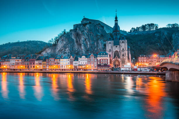 Historic town of Dinant with river Meuse at night, Wallonia, Belgium Classic view of the historic town of Dinant with scenic River Meuse in beautiful evening twilight light during blue hour at dusk, province of Namur, Wallonia, Belgium meuse river stock pictures, royalty-free photos & images