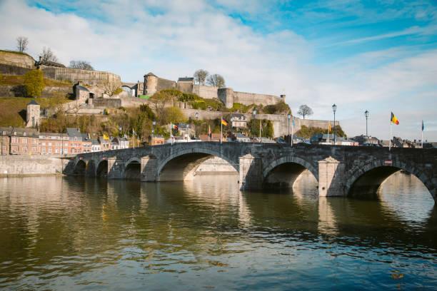 historische stad namen met de oude brug en de maas, wallonië, belgië - maasvallei stockfoto's en -beelden
