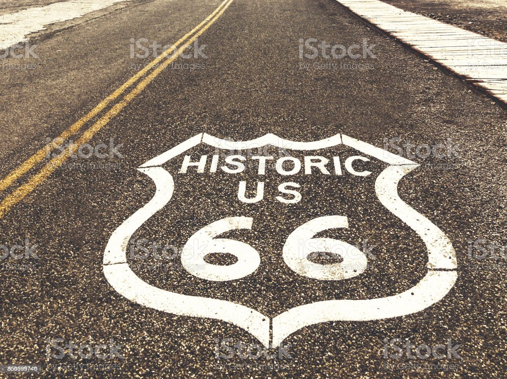 Historic US Route 66 highway sign on asphalt in Oatman, Arizona, United States. The picture was made during a motorcycle road trip through the south western states of USA. stock photo