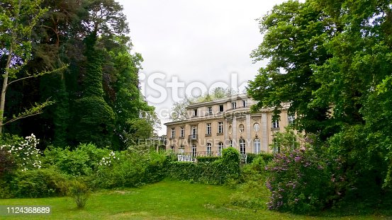 Wannsee, Berlin, Germany - May 24, 2017: Lake side view of the historic Wannsee villa, green garden on overcast day in summer. The Wannsee house is the famous historic villa in a Berlin suburb, where in 1942 a conference took place which led to the deportation of the Jews.  Now the house is a holocaust memorial and museum.