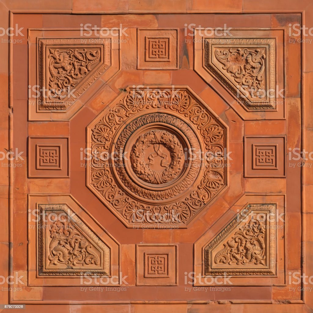 Historic wall with orange terracotta meander tile stock photo