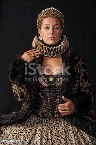 Portrait of a beautiful historical blonde Queen character wearing a period dress in a studio shot