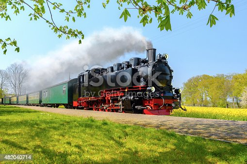 istock Historical German steam train passes through the fields in sprin 482040714