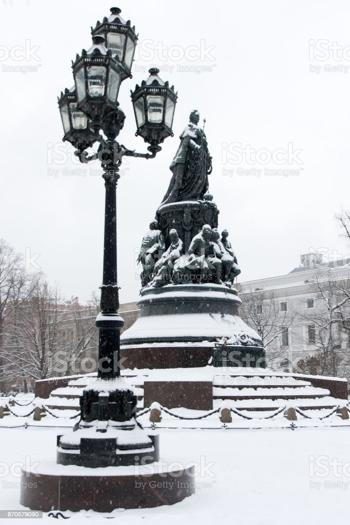 Historical landmark and touristic spot in Saint Petersburg, Russia: russian queen Catherine the Great monument in the Ostrovsky square by a winter day covered by snow with old vintage lantern near it. stock photo