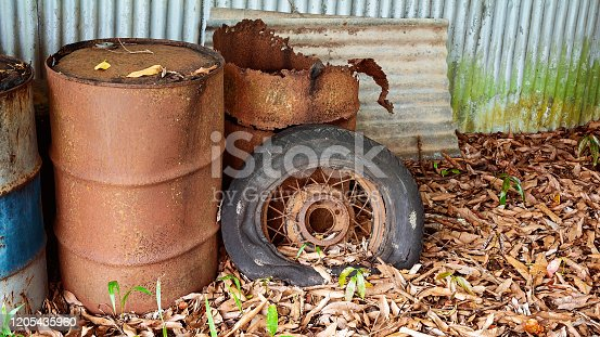 Old rusted forty four gallon drums and a car spoke tyre lying outdoor amongst leaves, on display as part of colonial farming of yesteryear